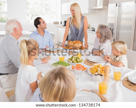 Family looking at the mother with a turkey plate for dinner - stock photo