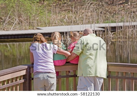 Family Looking at the Water on the Dock - stock photo