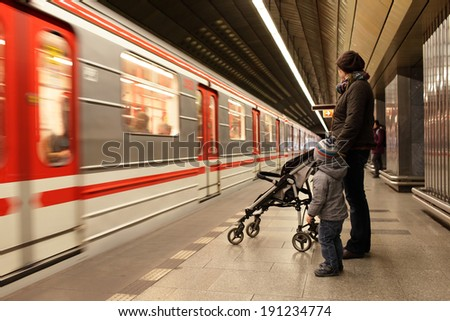 Family looking at train at subway station in Prague - stock photo