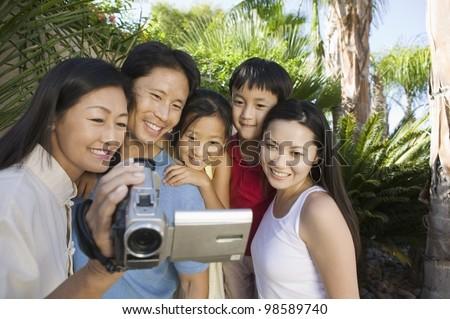 Family Looking at Video Camera Screen - stock photo