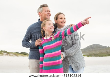 Family looking out towards the sea at the beach - stock photo