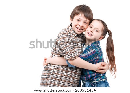 Family love. Small pretty girl standing near her older brother and hugging him while both are smiling and happy isolated on white background - stock photo