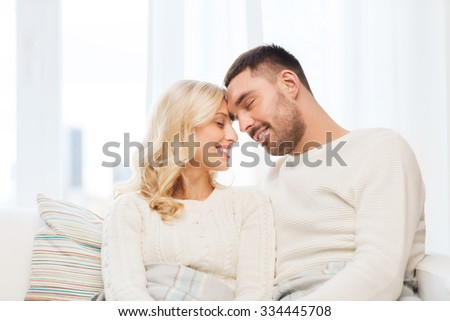 family, love, winter, holidays and people concept - happy couple covered with plaid sitting on sofa at home