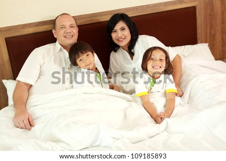 Family lying down in the bedroom