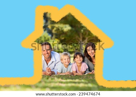 Family lying down in the park against house outline