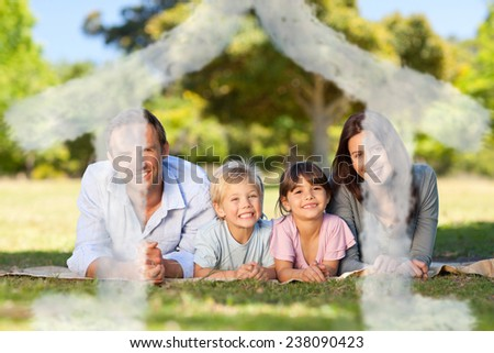Family lying down in the park against house outline in clouds