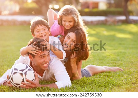 Family Lying In Pile Up On Grass Together - stock photo