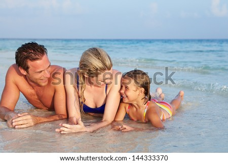 Family Lying In Sea On Tropical Beach Holiday - stock photo