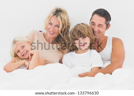Family lying on a white bed in the bedroom - stock photo