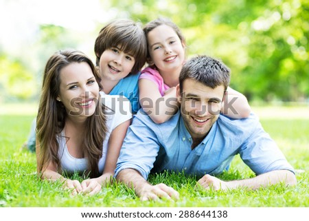 Family lying on grass - stock photo