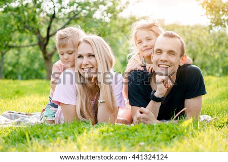 Family lying on grass in countryside - stock photo
