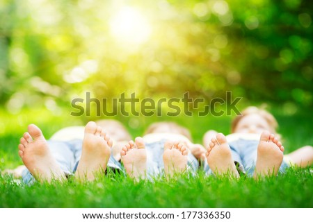 Family lying on green grass in spring park. Healthy lifestyle concept - stock photo