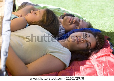 Family lying on sleeping bags in tent entrance on garden lawn, father and children sleeping, mother daydreaming, side view - stock photo
