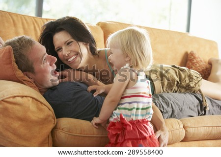 Family Lying On Sofa At Home - stock photo
