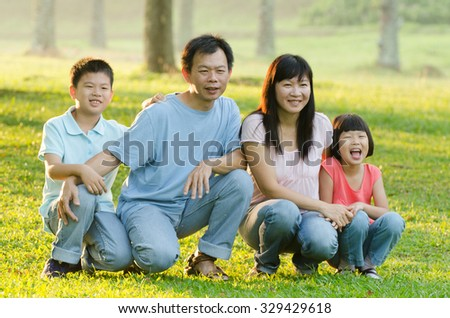 Family lying outdoors being playful and smiling, Outddor portrait
