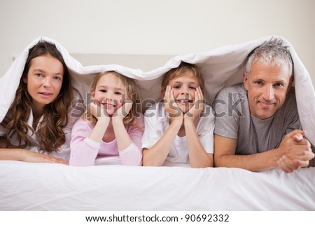 Family lying under a duvet in a bedroom