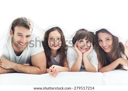 Family lying under the duvet  - stock photo