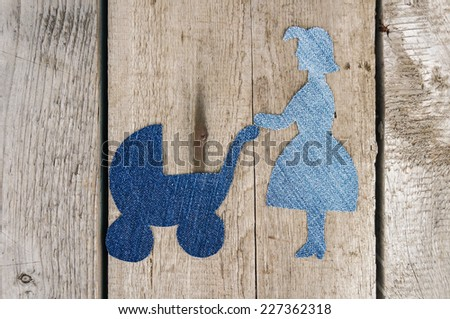 Family made from jeans fabric. Mother with pram on wooden background - stock photo
