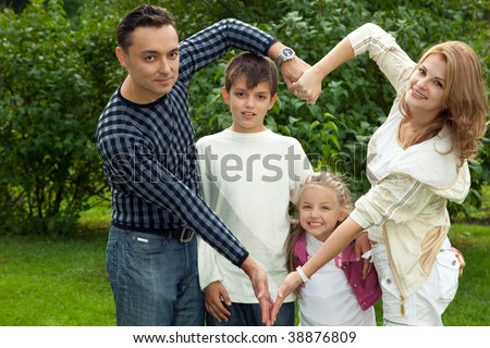 family making heart symbol from hands outdoors - stock photo
