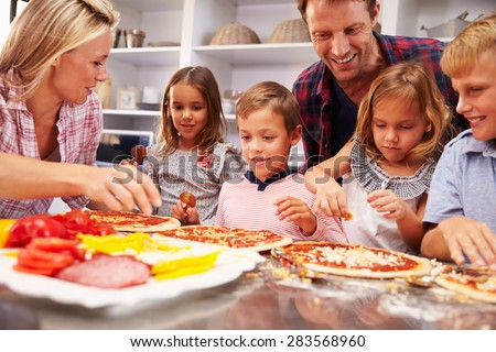 Family making pizza for dinner - stock photo
