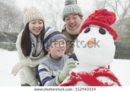 Family making snowman in a park in winter - stock photo