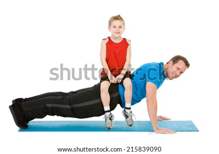 Family: Man Does Push-ups With Child Sitting On His Back  - stock photo