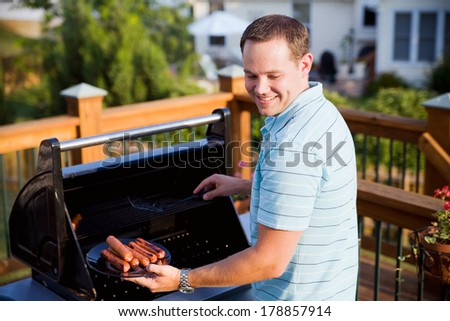 Family: Man Getting Hot Dogs From Grill On Porch - stock photo