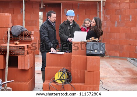 Family meeting with their architect - stock photo