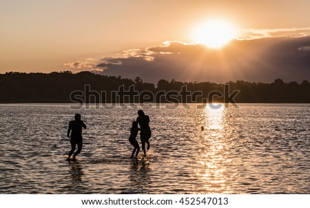 Family members are having fun at lake under sunset