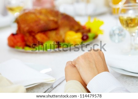 Family members giving thanks to God at festive table while holding each other by hands
