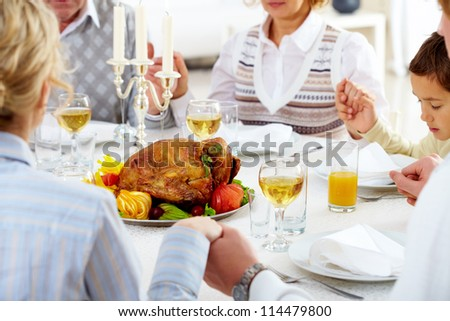 Family members giving thanks to God at festive table with roasted turkey on it - stock photo
