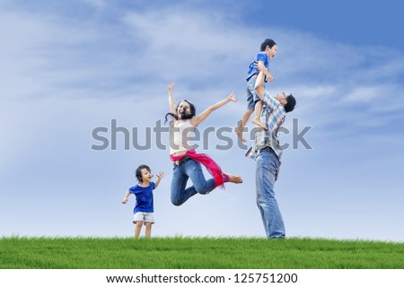 Family members including parents and two children are having fun at the park - stock photo