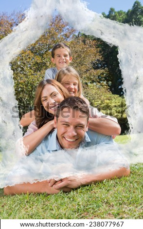 Family members lying on each other against house outline in clouds