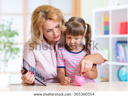 family - middle aged mother and kid daughter with pink piggy bank and calculator - stock photo
