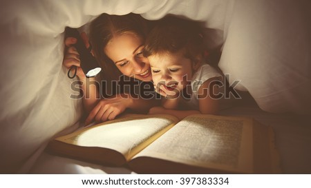 Family   Mom and child daughter reading a book with a flashlight under the blanket in bed - stock photo