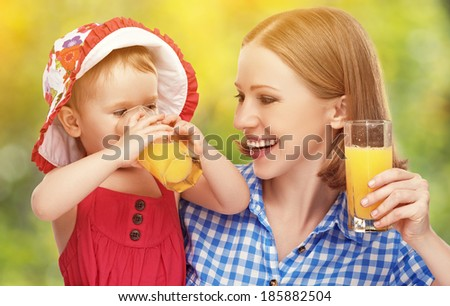 family mother and baby daughter drinking orange juice in the summer outdoors - stock photo