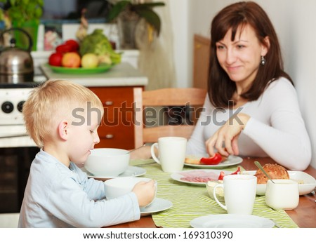 Family mother and blond son boy kid child eating corn flakes and bread together breakfast morning meal at the table. Home. - stock photo