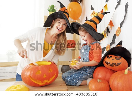 family mother and child daughter in hat witch are preparing for Halloween carve a pumpkin and decorate the house