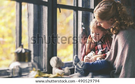 family mother and child daughter keep warm and look out the window on a rainy autumn day
