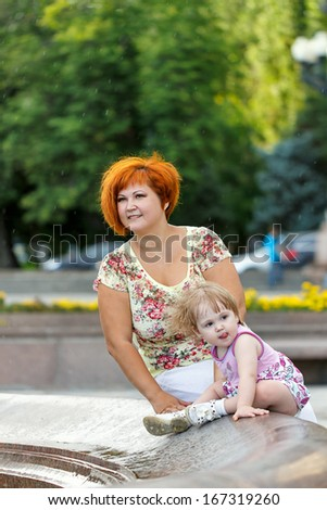 Family, mother and daughter are sitting on the edge of a fountain in a city park - stock photo