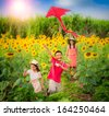 Family mother and son in summer playing with kite with sun flower garden - stock photo