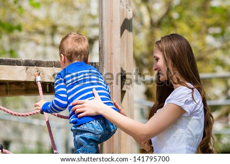 Family - Mother and son playing on a jungle gym - stock photo