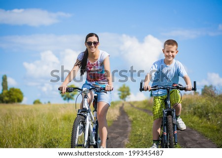 family. mother and son riding  in the park
