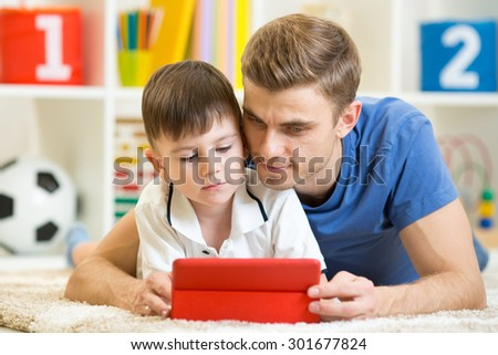 Family - mother and son with tablet on floor at home. Woman and child boy relaxing at tablet computer. - stock photo