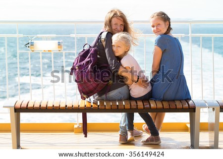 family - mother and two daughters sitting on a bench on the ferry and the sea in the background - stock photo