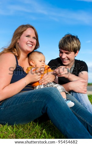 Family - mother, father and child sitting and playing in garden