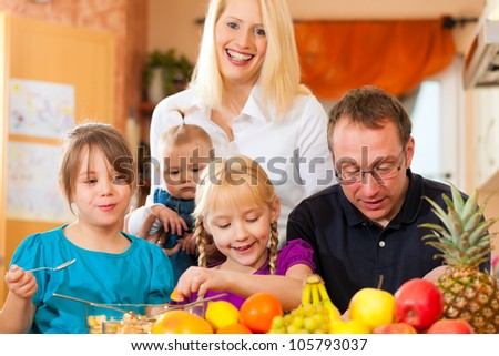 Family (mother, father and children) with lots of fruits for breakfast food, this is healthy nutrition