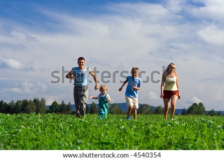 family mother father and two child run on field under blue sky - stock photo