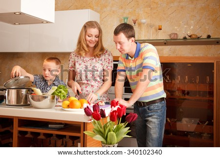 Family - mother,father and 7 year old son  are cooking together in the kitchen - stock photo