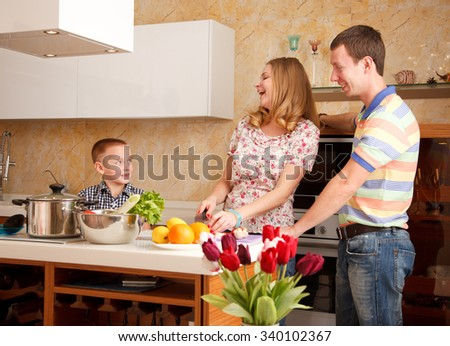 Family - mother,father and 7 year old son  are cooking together in the kitchen